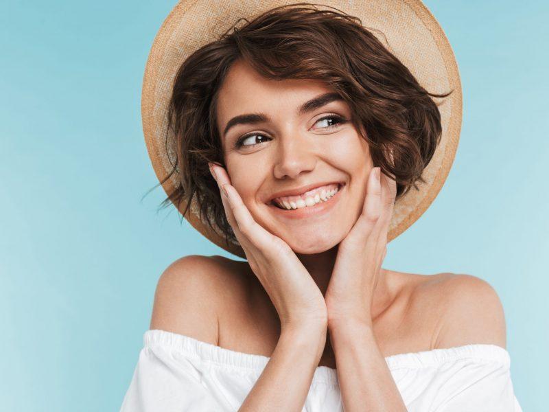 Close up of a smiling young woman in summer hat looking away isolated over blue background